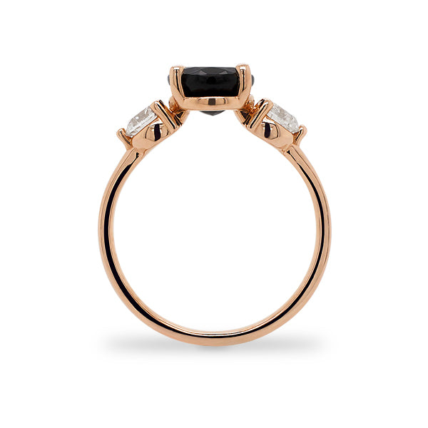 Side view of oval cut black sapphire and round cut diamond ring set in 14 kt rose gold.
