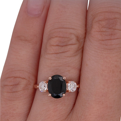 Oval cut, black sapphire and diamond ring set in 14 kt rose gold worn on left ring finger from King + Curated in Beacon, NY.