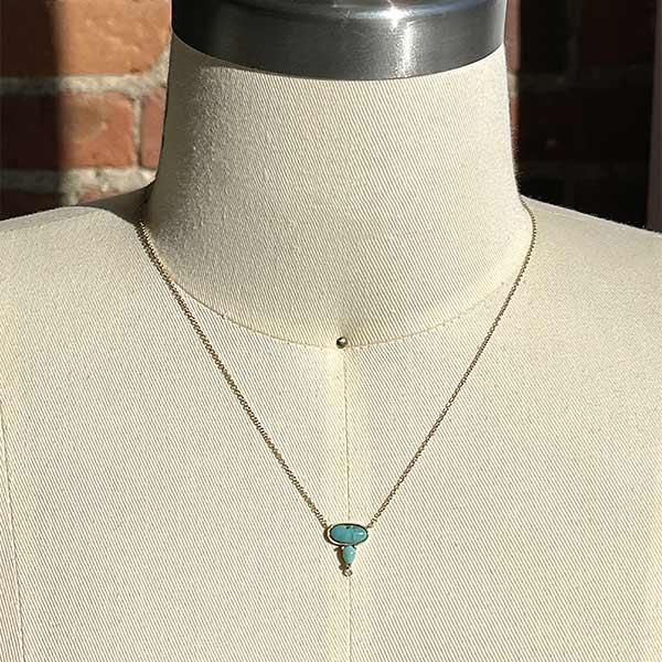 Load image into Gallery viewer, Oval and pear cut turquoise and round diamond necklace cast in 14 kt yellow gold on a body form.