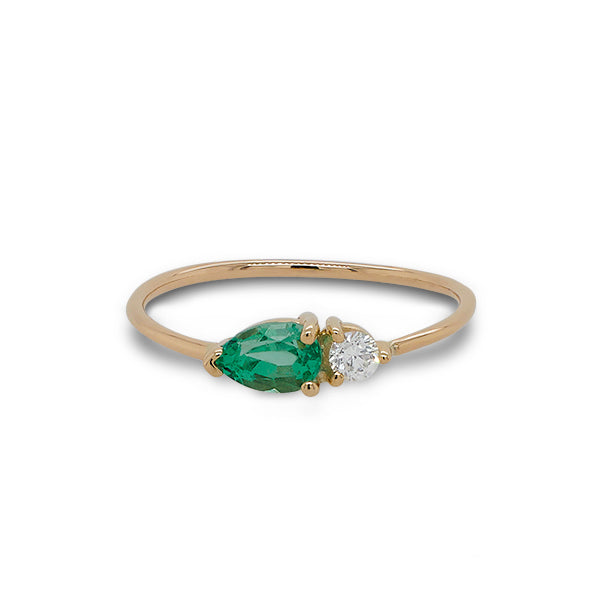 Front view of pear cut emerald and round diamond ring cast in 14 kt yellow gold.
