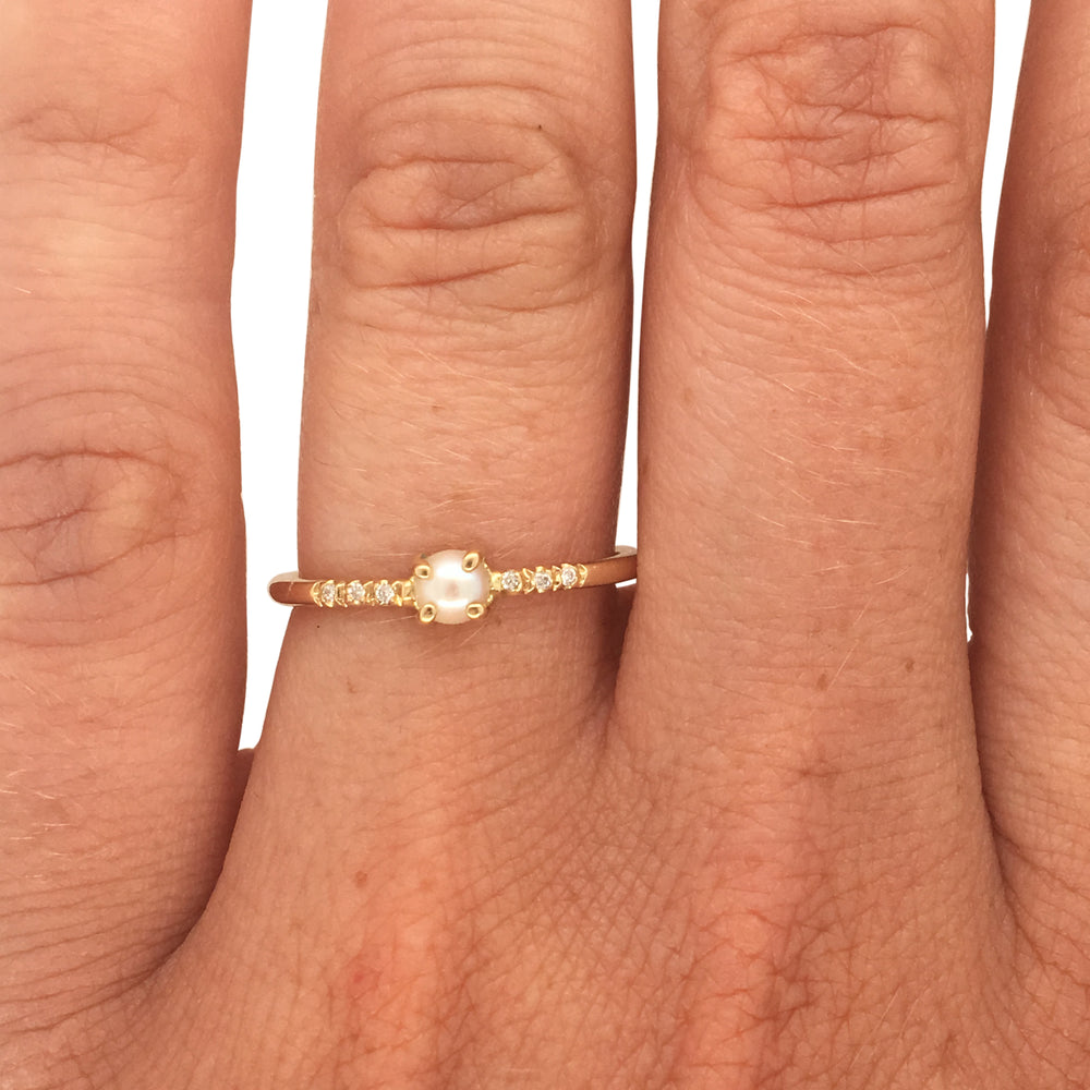Pearl and diamond ring cast in 14 kt yellow gold on left ring finger.
