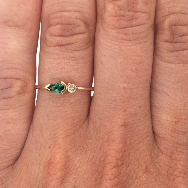 Pear cut, green tourmaline and diamond ring cast in 14 kt yellow gold on left ring finger.