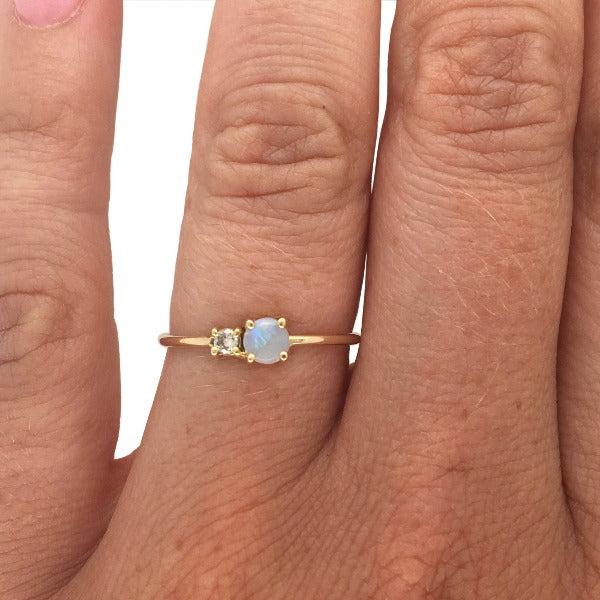 Load image into Gallery viewer, Petite moonstone and round diamond ring set in 14 kt yellow gold on left hand ring finger.