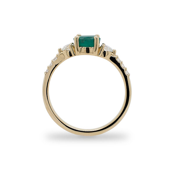 Side view of round emerald ring with 2 medium and 6 small accent diamonds cast in 14 kt yellow gold.