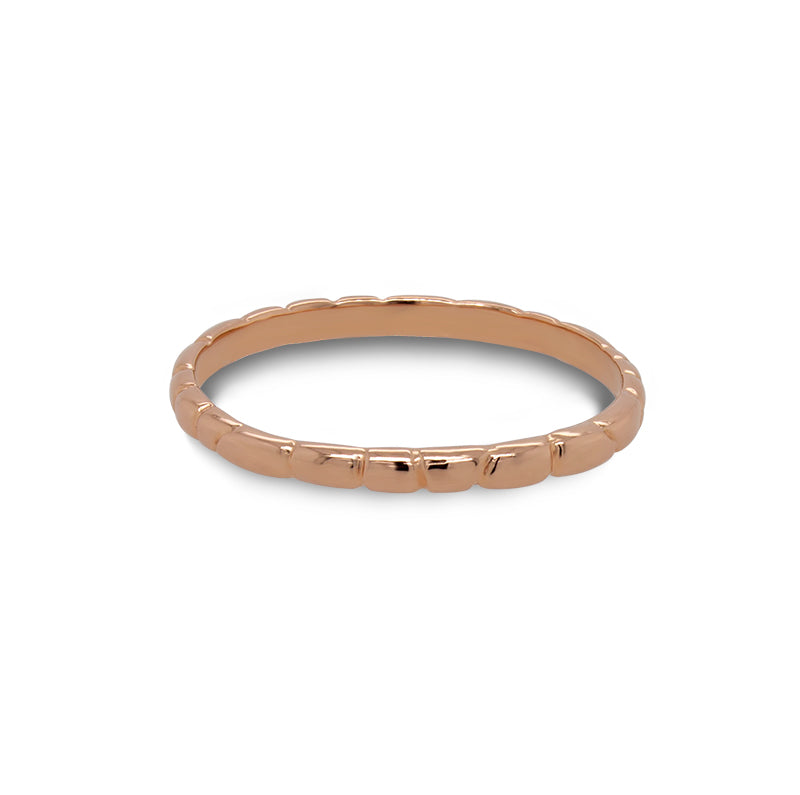 Front view of a stacking band with organic spaced lines casted in 14 kt rose gold.