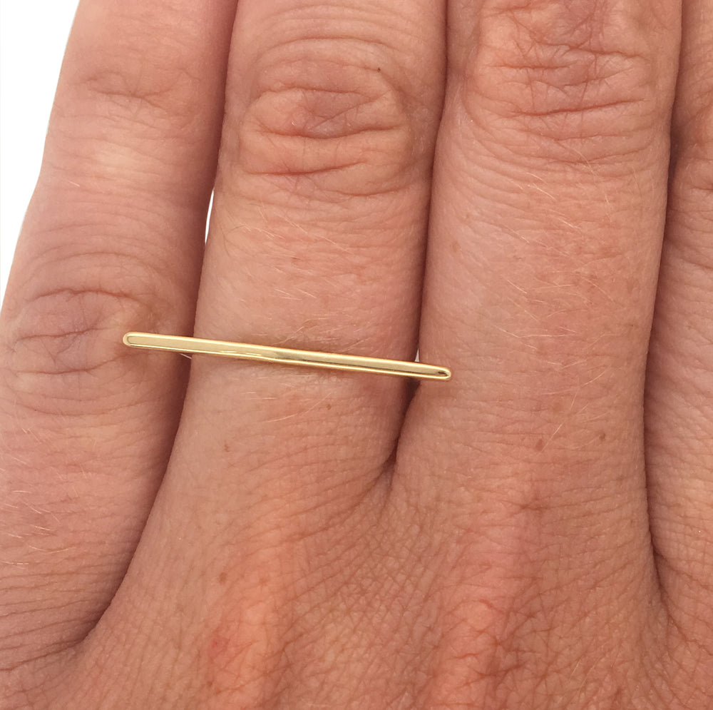 Load image into Gallery viewer, Bar shaped ring cast in 14 kt yellow gold on left ring finger.