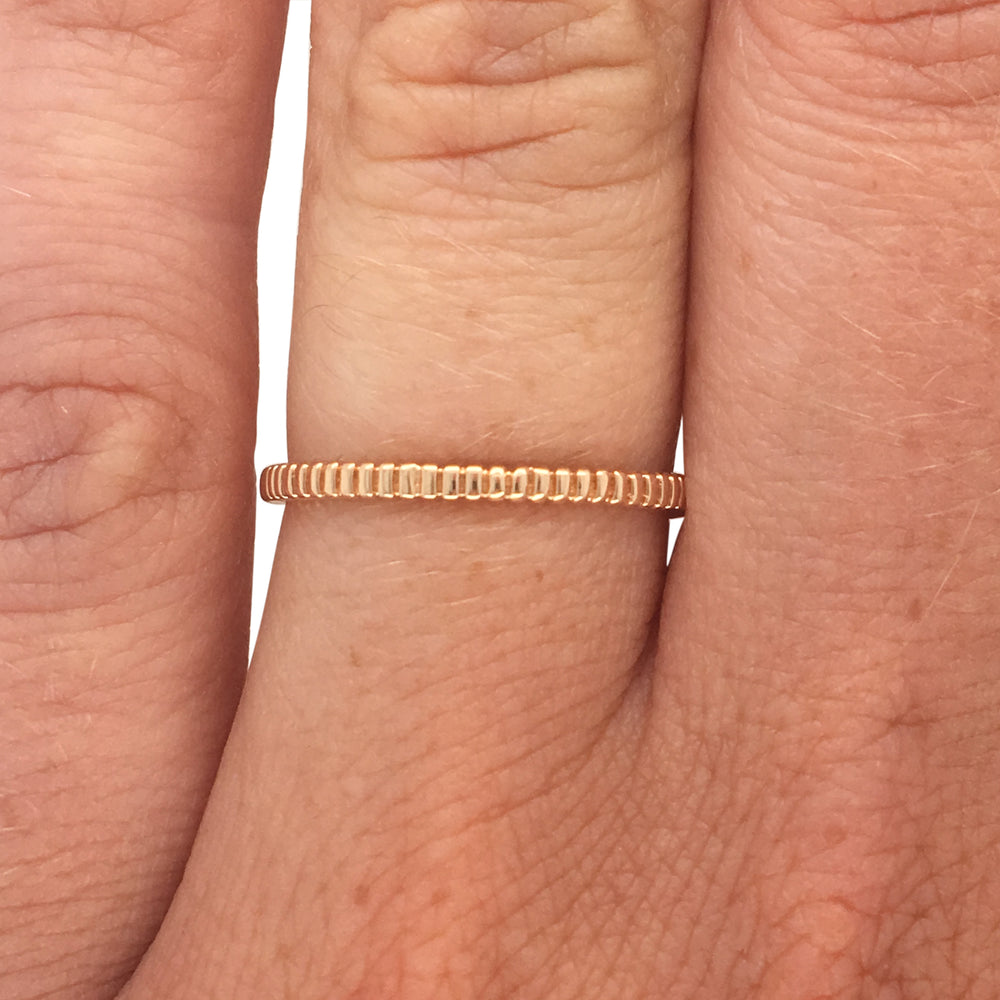 Load image into Gallery viewer, Ring with a lined pattern cast in 14 kt yellow gold on left ring finger.