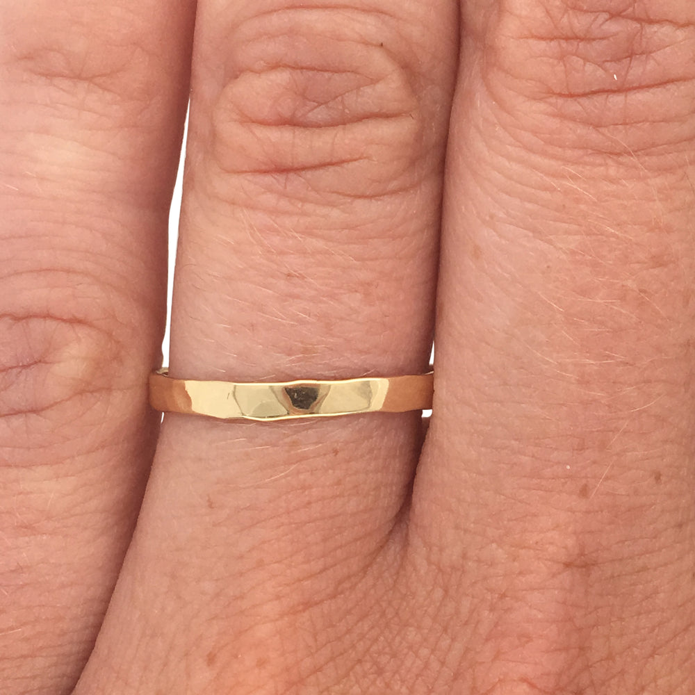 Load image into Gallery viewer, Hammered stacking band cast in 14 kt yellow gold on left ring finger.