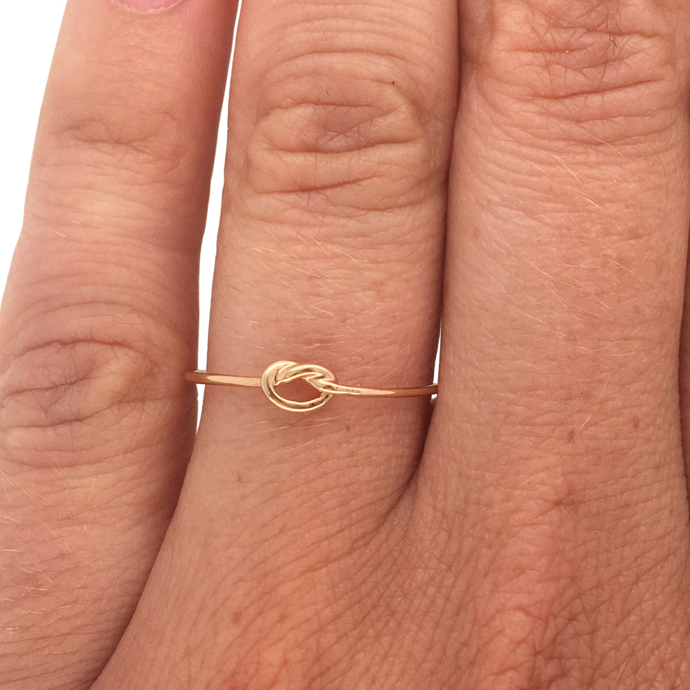 Small stacking band with a center knot casted in 14 kt yellow gold on left ring finger.