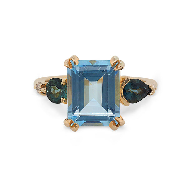 Front view of a large, emerald cut topaz, tourmaline and diamond ring cast in 14 kt yellow gold.