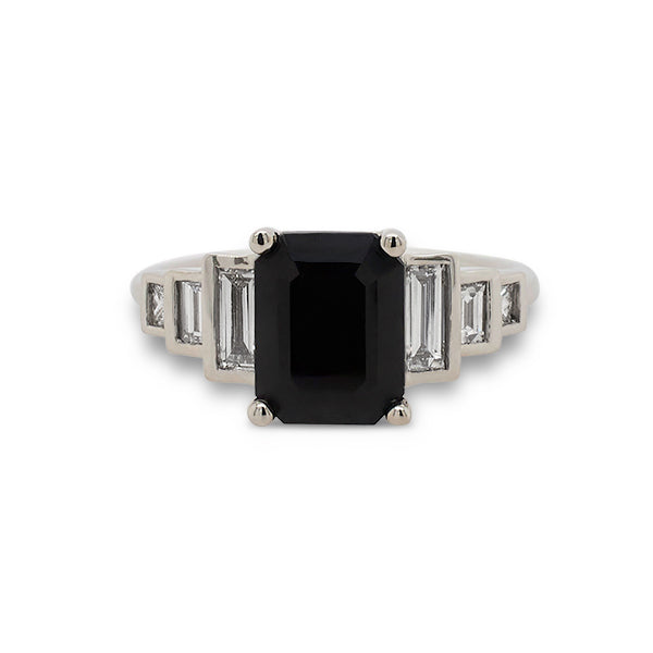 Front view of emerald cut black sapphire ring with 6 baguette cut diamonds set in 14 kt white gold.