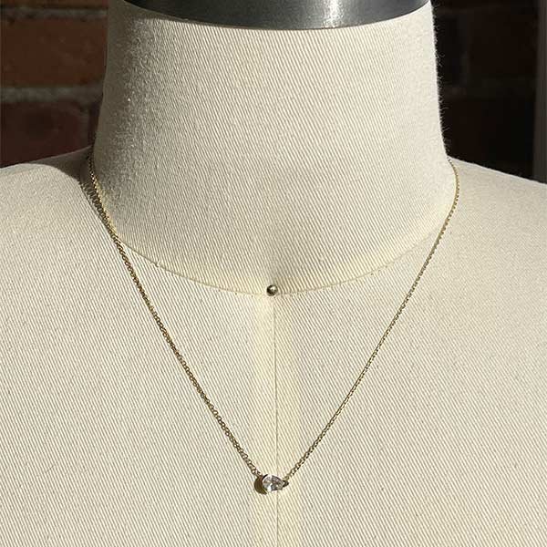 A pear cut white sapphire pendant necklace cast in 14 kt yellow gold on a body form for scale.