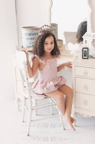 An adorable romper with vintage charm. Frayed ruffled shoulder edges and layers of lace across the bodice. Full Boomer bottoms. Attachable rosette clip. Image by Sincerely Jane Photography