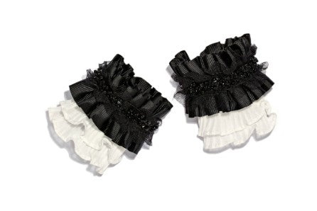 Modern Queen Kids Queen's Knight girl's cuffs in black and white. Features white pleated ruffles, black grosgrain pleating, and black and white tulle trim.