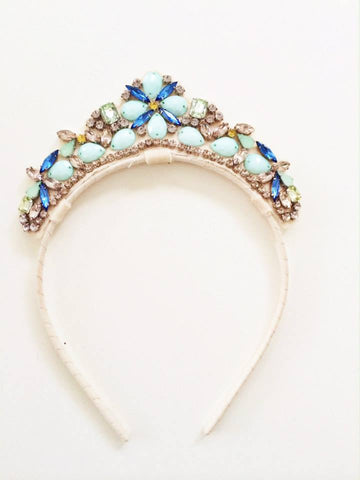 Our beautiful Abbey Jeweled Crown Tiara is a perfect addition for your next photo shoot or special event. It's blue, minty green and crystal gems are sure to dazzle. Available for rent today from The Borrowed Boutique.