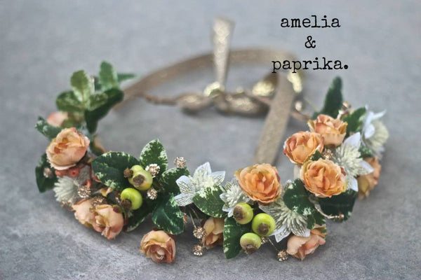 A lush Amelia and Paprika halo filled with soft peach flowers, gold accents, and greenery. Custom made for our shop and adjustable in size due to the tie back ribbons. One size fits most.