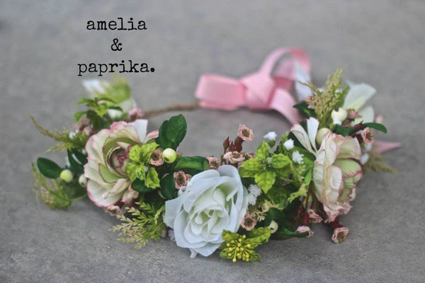 A lush Amelia and Paprika halo filled with soft pink and white flowers and greenery. Custom made for our shop and adjustable in size due to the tie back ribbons. One size fits most.