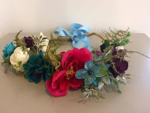 Amelia and Paprika flower halo filled with vibrant flowers in darker hues such as pink, teal and purple along with the right touch of greenery. Custom made for our shop and adjustable in size due to the tie back ribbons. One size fits most.