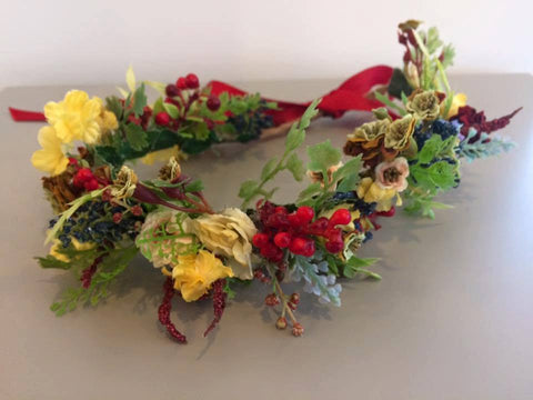 Amelia and Paprika flower halo filled with vibrant flowers in yellows, reds, and blues and greenery. Custom made for our shop and adjustable in size due to the tie back ribbons. One size fits most.