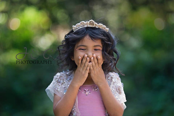 A sparkly tiara in creams, nude, and soft pink. One size fits most. Starting at toddler size through girls.