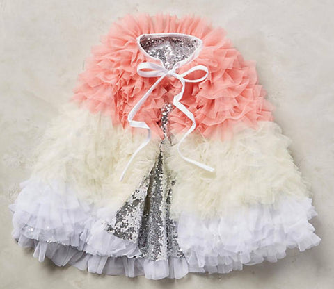 Circus Cape in dazzling white, cream, blush, and silver ruffles. One size fits most. Available for rent from The Borrowed Boutique.