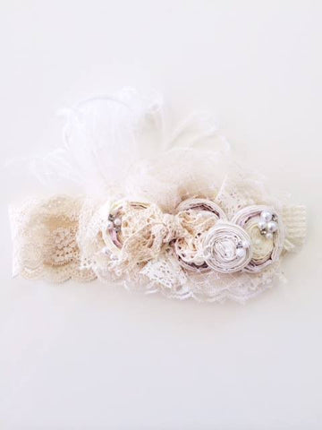 A stunning statement headband by Dollcake. Soft creams and misty pinks with feather and pearls. One size fits most. Works well on toddler and up.