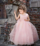 A little girl is wearing the Dollcake Pink Perfection Frock. The dress is made with layers of soft pink tulle with cascading flowering petals and has a soft cotton bodice.