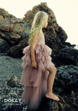 Little blonde girl standing on a rock wearing the Dolly by Le Petit Tom Daring High-Low Dress in Dusty Pink.