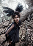 Little girl wearing the Tutu Du Monde Raven Wings Dress In Black and a feather headpiece.