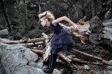 A girl jumping in the woods is wearing the Tutu Du Monde Black Bird Tutu Dress In Night Sky