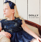 Little girl in navy bow wearing the DOLLY by Le Petit Tom Drama Dress in Navy available for rent from The Borrowed Boutique.