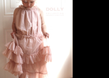 Little girl wearing the Dolly by Le Petit Tom Ruffled Chiffon Dance Dress In Ballet Pink available for rent from The Borrowed Boutique.