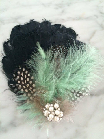 Custom feather clip in mint, black, taupe, and white. One size fits most. Available for rent from The Borrowed Boutique.