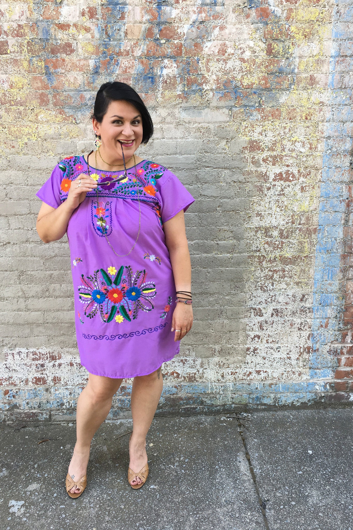 ShopMucho models women's Mexican dress in purple with embroidered flowers