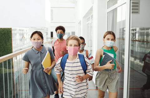 Kids in masks running through school hallway, carrying notebooks and backpacks