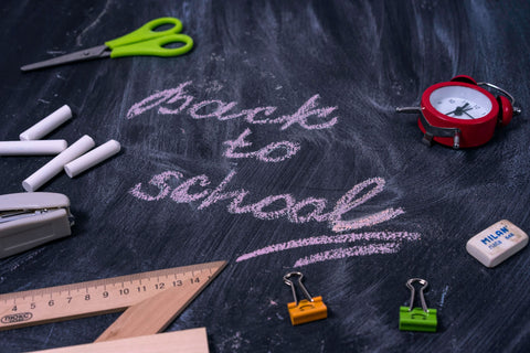 Back to school written in pink on a chalkboard with scissors, rulers, erasers, a red alarm clock, stapler and green and orange clips