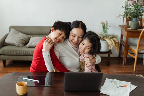Mother hugs two children while sitting in front of a desk. The desk has papers, a coffee mug, tablet, laptop scattered on top.