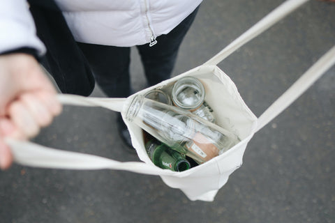 Woman holds a reusable bag filled with bottles for recycling