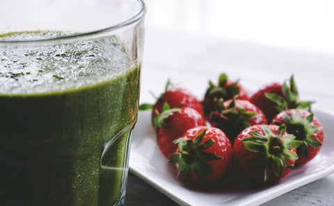 Glass of green smoothie next to bowl of strawberries