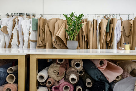 Rolls of different colored fabrics sit in a wooden shelf. Beige and white material hangs on a rack in the background. A green plant sits on a marble table.