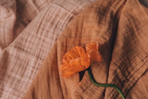 Orange and pink fabric sit beneath an orange flower with a green stem.