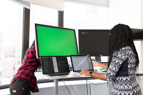 A computer monitor with a green screen and people working around it.