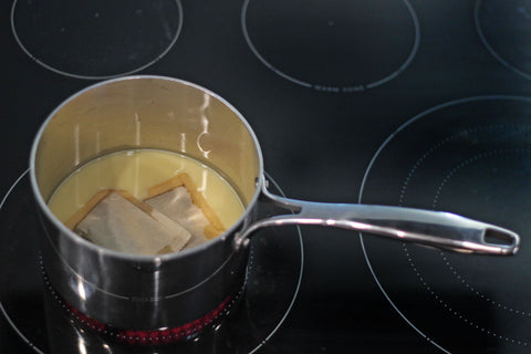 A pot sits on the stove and bring milk, dates, cinnamon sticks, and a tea bag to a boil.