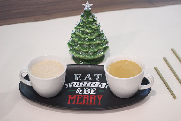 """Two tea mugs sit on top of a tray that says """"Eat, Drink, & Be Merry."""""""
