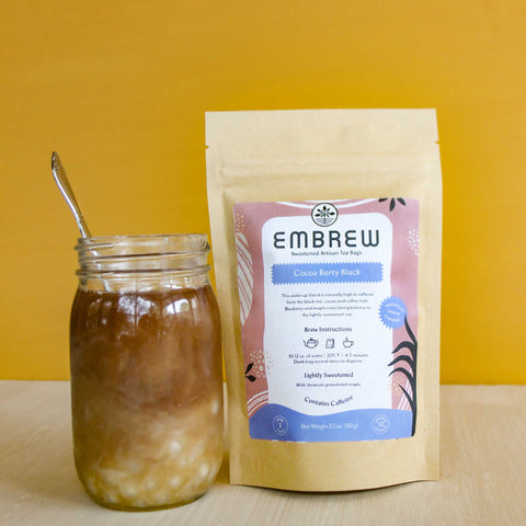 A pouch of Embrew's Cocoa Berry Black tea and a glass of boba bubble tea.