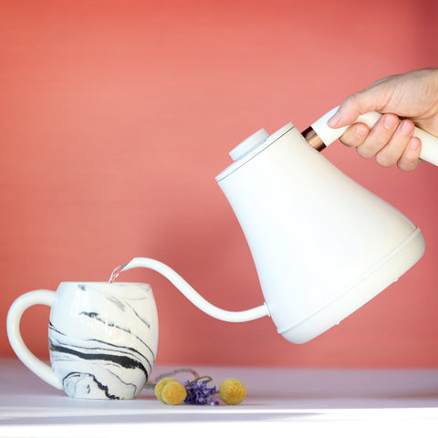 A Gooseneck Electric Tea Kettle pours boiling water into a tea mug on top of a counter.