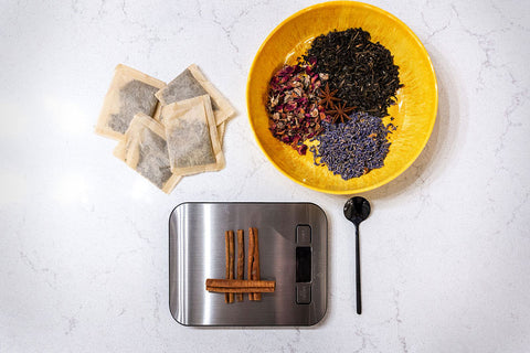 A food scale weighs some cinnamon sticks beside a teaspoon, a bowl of tea leaves, and a handful of tea bags.