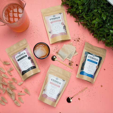 Four cold brew tea blends sit on top of a peach pink background beside teaspoons, tea bags, a pitcher, and a glass.