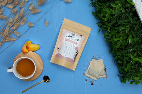A pouch of Embrew's Summer Peach Rooibos sits on a blue bakcground with two tea bags, a mug, some peaches, and a teaspoon.