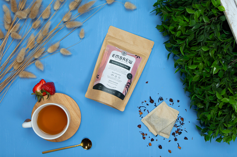 A pouch of Embrew's Strawberry Yaupon Hops Sweetened Tea on a blue background beside two tea bags, a teaspoon, and a tea cup.